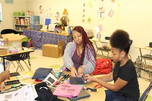 Timiya Burgwyn and Armani Johnson are cooperatively designing and constructing an electric car.